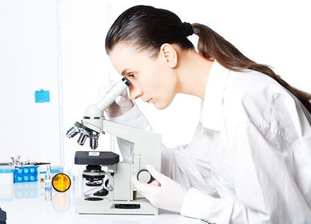 Scientifique regardant à travers un microscope dans un laboratoire