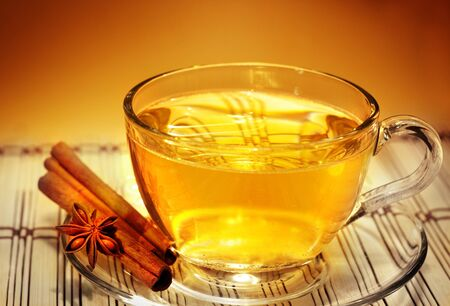christmas tea: glass of aromatic tea in the warm soft evening light