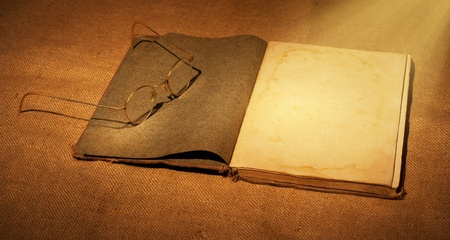 old book and glasses in ambient light photo