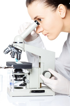 Scientist looking through a microscope in a laboratory photo
