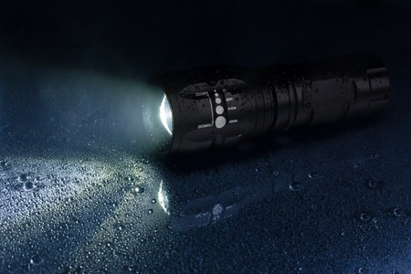 tactical: Tactical waterproof flashlight with waterdrops and smoke Stock Photo