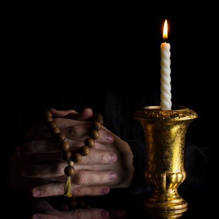 clasped: Prayer hands with rosary and vintage candle on black