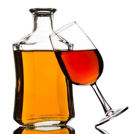 botella de licor: Botella de coñac y el vidrio aislado en blanco Foto de archivo