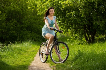 Happy girl over a bicycle on forest pathway photo