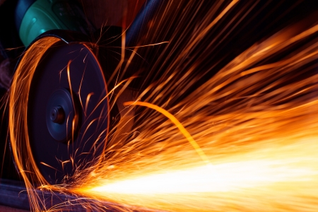 welding worker: Sparks while grinding iron