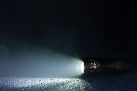 taschenlampe: Tactical wasserdichte Taschenlampe mit Wassertropfen und Rauch Lizenzfreie Bilder
