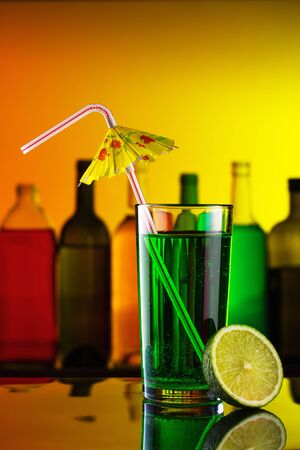 Alcohol cocktail with straw and lime on bar photo