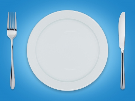 Empty clean dinner plate with knife and fork