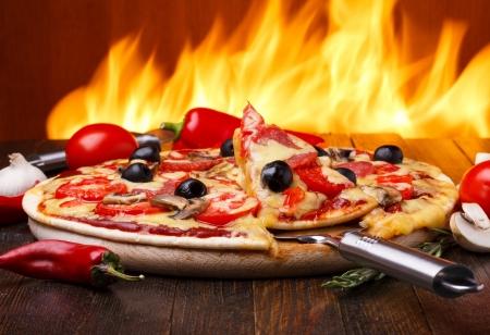 Gorąca pizza z pieca na tle pożaru