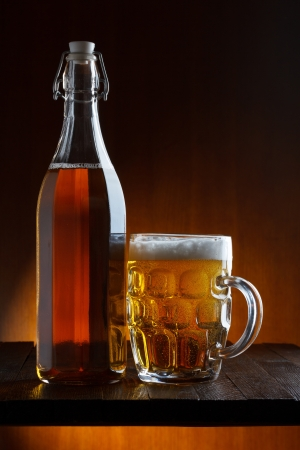 Beer bottle and mug on wooden table still life photo