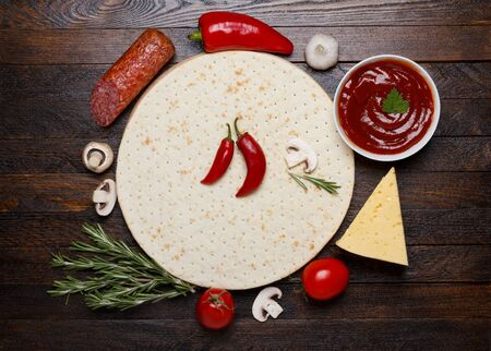 kitchen table top: raw pizza ingredients - dough, sauce, cheese, mushrooms, salami and tomato Stock Photo