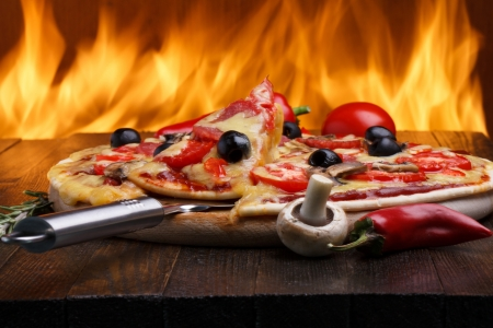 Hete pizza met oven brand op achtergrond Stockfoto