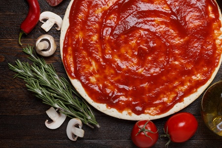 Fresh pizza dough with tomato sauce and natural ingredients for cooking on wooden table Stock Photo
