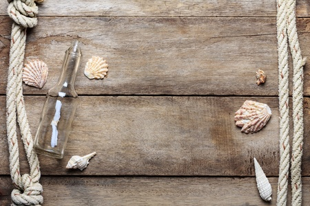bootle: Weathered vintage wooden background with bootle, ropes and shells