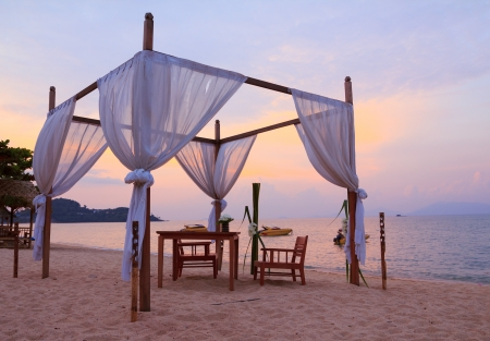 Romantic table setting on the beach at sunset Imagens
