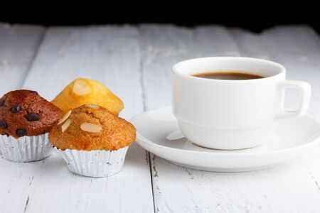 Coffee with cupcakes on wooden table photo