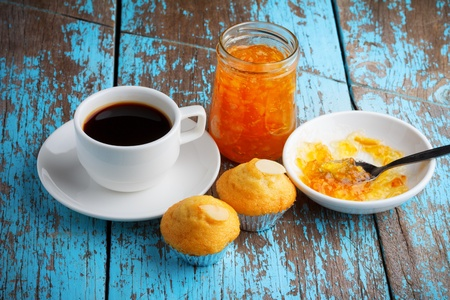 Cupcake with jam and coffee on old wooden table photo