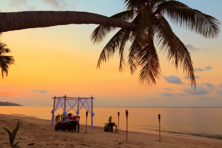 Romantic table setting on the beach at sunset photo