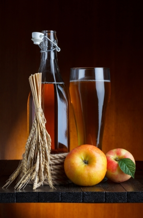 apple cider glass and bottle with apples and wheat still life photo