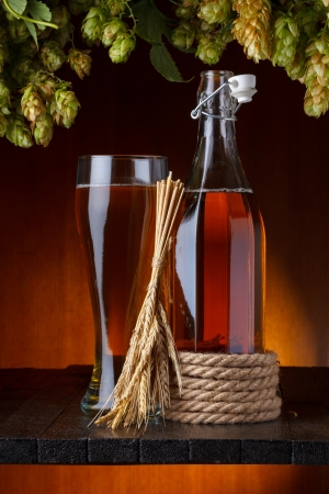 Beer with hop and wheat on wooden table still life photo