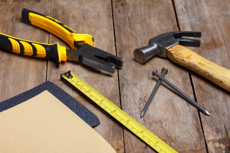 hardware tools: Construction instruments on wooden table - sandpaper, pliers, measuring tape, hammer, nails