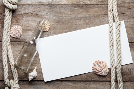 Blank paper sheet on weathered wood background with rope, shells, and bottle Imagens
