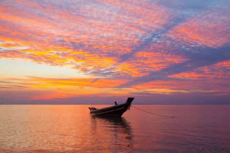 Small wooden fisherman boat at sunset photo