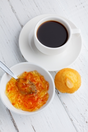 Cupcake with jam and coffee on wooden table photo