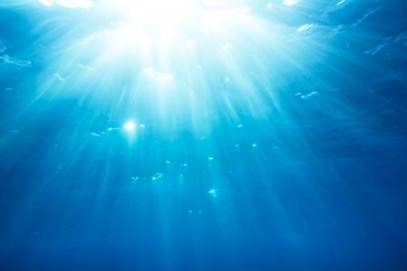 Onderwater geschoten met zonnestralen en vissen in de diepe tropische zee