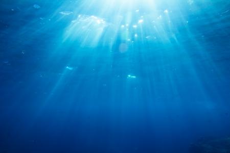 Podvodní shot s slunečních paprsků a ryb v hlubokém tropickém moři Reklamní fotografie