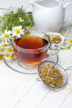 Chamomile tea and dried flowers on wooden table photo
