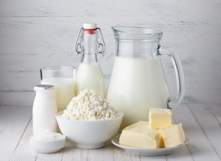 乳製品、牛乳、カッテージ チーズ、ヨーグルト、サワー クリーム、木製のテーブルにバターを塗る