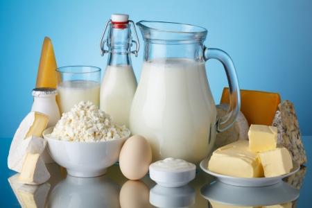 Mléčné výrobky, mléko, sýry, vejce, jogurt, zakysaná smetana, tvaroh a máslo na modrém pozadí zátiší