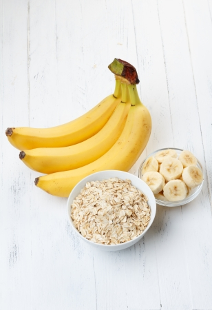 Bowl of oat flakes with sliced banana on wooden table Imagens
