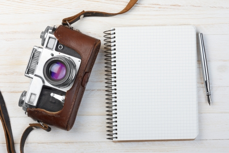Blank notebook with fountain pen and retro camera on wooden table photo