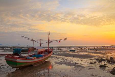 shore line: Small wooden boat with light bulbs for night squid fishing on the shore during ebb tide, Thailand Stock Photo