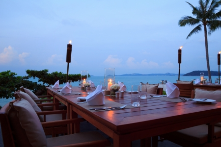 Romantic dinner setting at the beach on sunset, outdoor restaurant tables photo