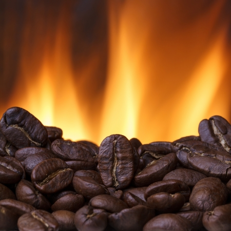 large bean: Coffee beans roasting with fire on background Stock Photo