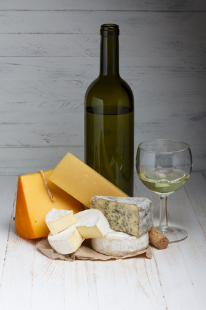 White wine and cheese on wooden table photo