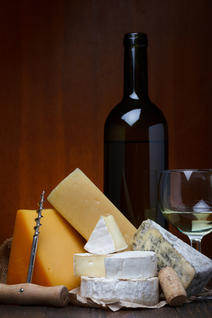Cheese assortment and wine on wooden table still life photo