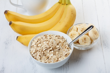 Bowl of oat flakes with sliced banana close-up on wooden table