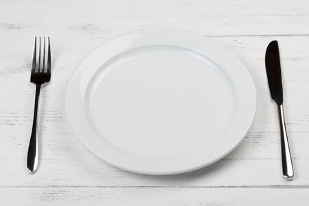 Empty clean plate with fork and knife on wooden table, focus on front part photo