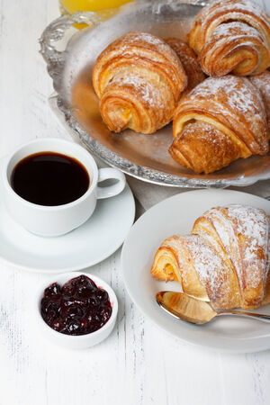 Croissants with jam and coffee on wooden table still life photo