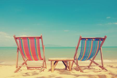 Vintage tónovaný dvě plážová lehátka na tropickém pobřeží