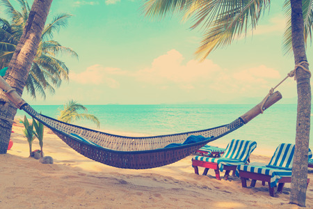 Vintage gestileerd hangmat onder palmbomen op zonnige tropisch strand Stockfoto