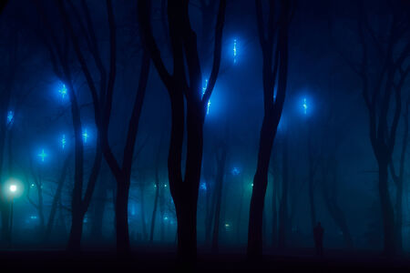 ghost town: Dark mystery city park decorations in fog with some people silhouette Stock Photo