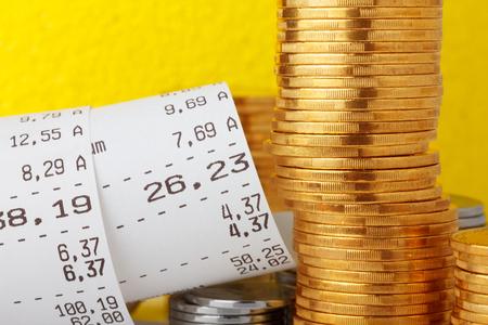 cash receipt: Cash register paper receipt check with coins stack closeup