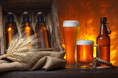 Beer glasses with wooden crate full of beer bottles and wheat ears on table photo