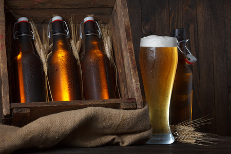 Beer glass with wooden crate full of beer bottles and wheat ears photo