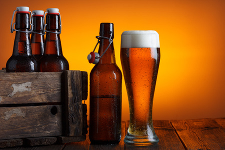 Beer glass with wooden crate full of beer bottles on table photo